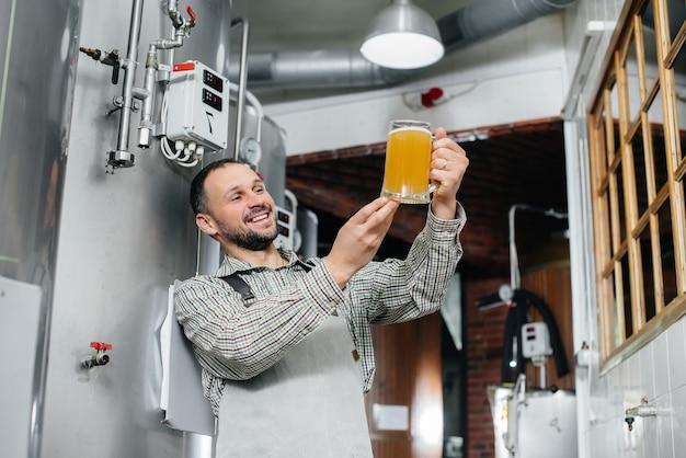 Een jonge, bebaarde brouwer voert de kwaliteitscontrole uit van vers gebrouwen bier in de brouwerij.