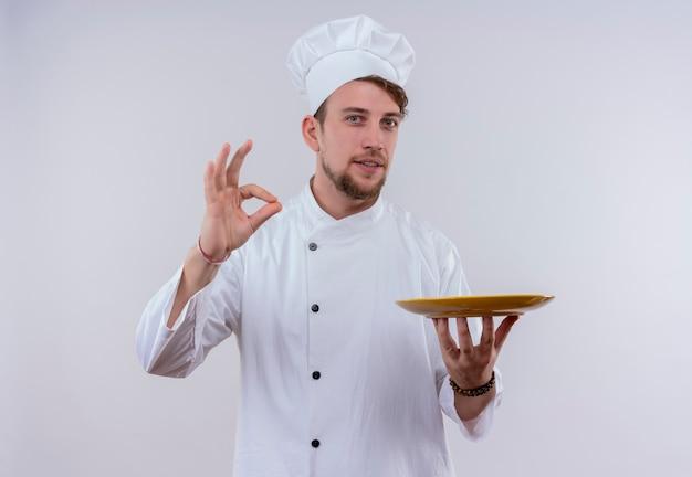 Een jonge, bebaarde chef-kok die wit fornuisuniform en hoed draagt en lekker ok teken met vingers toont met gele kom op zijn hand terwijl hij op een witte muur kijkt