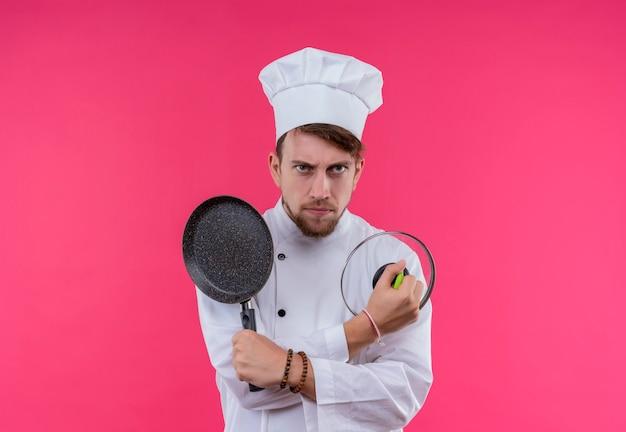 Een jonge, bebaarde chef-kok in wit uniform houdt een koekenpan met deksel vast terwijl hij met een boze uitdrukking op een roze muur kijkt