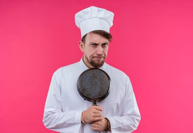 Een jonge, bebaarde chef-kok in wit uniform houdt een koekenpan vast terwijl hij met een boze uitdrukking op een roze muur kijkt