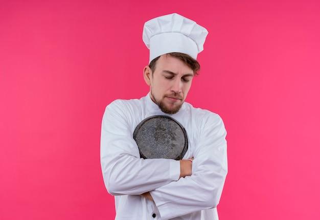 Een jonge bebaarde chef-kok man in wit uniform knuffelen koekenpan met gesloten ogen op een roze muur
