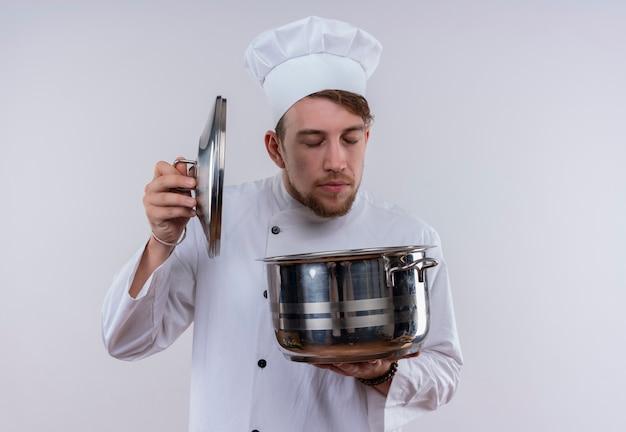 Een jonge, bebaarde chef-kokmens die een eenvormig wit fornuis draagt en een hoed die een kookpan op een witte muur ruikt