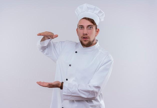 Een jonge, bebaarde chef-kokmens die een wit fornuisuniform draagt en een hoed gebaart met handen groot en groot formaat bord terwijl hij op een witte muur kijkt