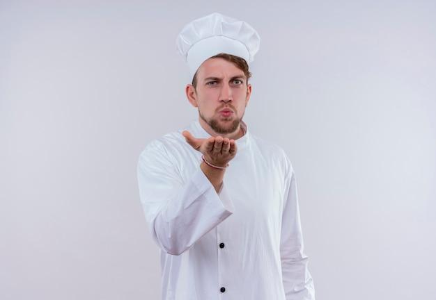 Een jonge, bebaarde chef-kokmens die een wit fornuisuniform en een hoed draagt en een kus verzendt terwijl hij staat en op een witte muur kijkt
