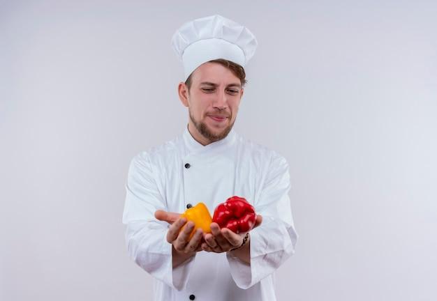 Een jonge, bebaarde chef-kokmens die wit fornuisuniform en hoed draagt die gele en rode paprika's op zijn hand op een witte muur bekijken