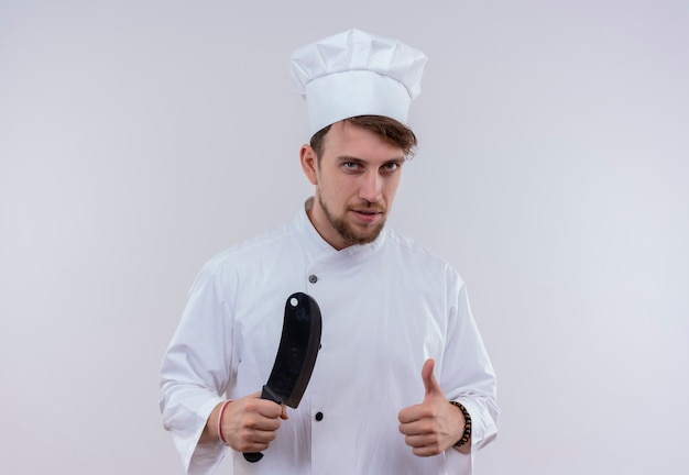 Een jonge, bebaarde chef-kokmens in wit uniform die vleesmes houdt en duimen toont terwijl hij op een witte muur kijkt