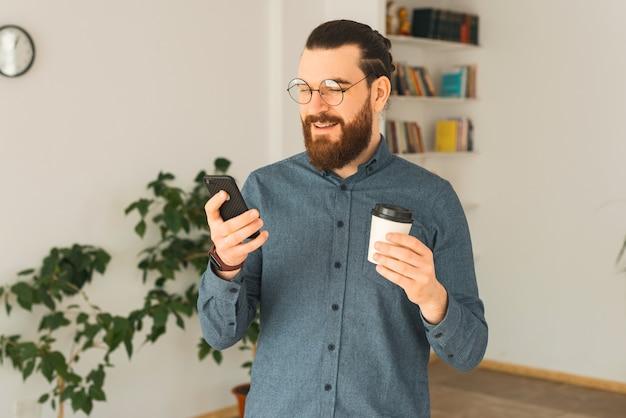Een jonge bebaarde hipster in kantoor drinkt koffie en praat over zijn telefoon