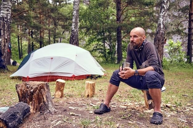 Een jonge, bebaarde man drinkt thee tijdens een kampeertrip, in de natuur, tegen de achtergrond van een toeristische tent.