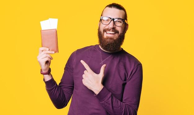Een jonge, bebaarde man houdt een paspoort vast met een paar kaartjes erin en wijst ernaar glimlacht