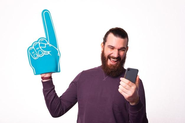 Een jonge, bebaarde man houdt een telefoon en een ventilatorhandschoen vast die naar de telefoon glimlacht bij een witte muur