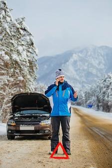 Een jonge, bebaarde man in de bergen in de winter had de auto moeten kapot maken en moet telefonisch om hulp hebben gevraagd