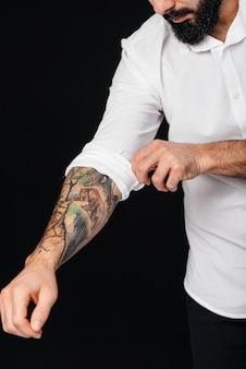 Een jonge bebaarde man in een wit overhemd en tatoeages staat op een zwarte achtergrond.