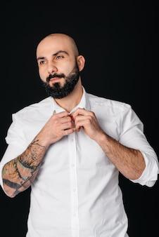 Een jonge bebaarde man in een wit overhemd en tatoeages staat op een zwarte muur.
