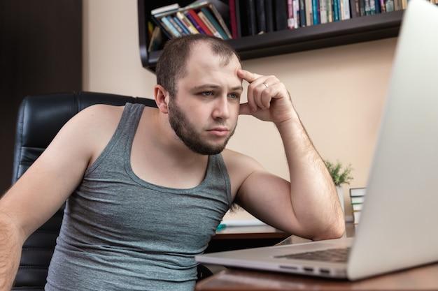 Een jonge, bebaarde man in huiskleren grijs t-shirt, gebruikt laptop