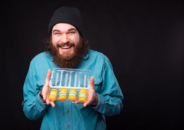 Een jonge, bebaarde man kijkt opgewonden naar de camera omdat hij een doos met kleurrijke bitterkoekjes vasthoudt