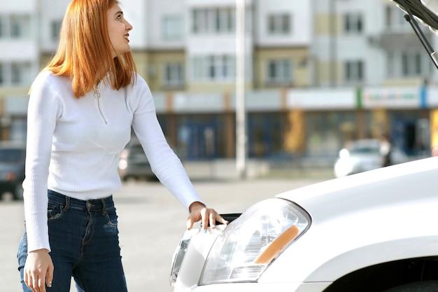 Een jonge bestuurder bij een kapotte auto met een kapotte kap