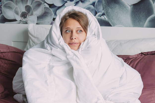 Een jonge bevroren grappige vrouw verstopt zich onder een warme deken om te ontsnappen aan de kou zittend op het bed
