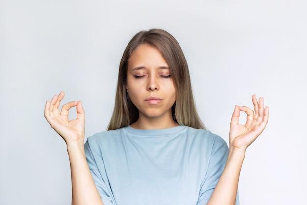 Een jonge blanke, bedachtzame blonde vrouw houdt de handen in mudra-gebaar met haar ogen dicht