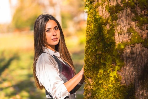Een jonge blanke brunette, in een park naast een boom op een herfstmiddag