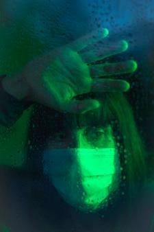 Een jonge blanke brunette met gezichtsmasker kijkt uit het raam in de covid19 quarantaine, met groen omgevingslicht