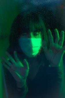 Een jonge blanke brunette met gezichtsmasker op zoek naar de covid19 quarantaine, met groen omgevingslicht