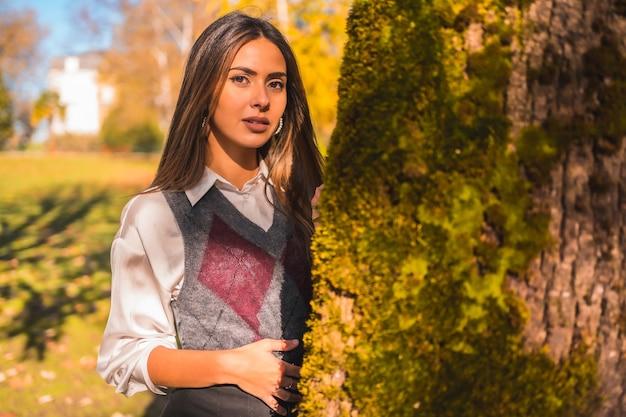 Een jonge blanke brunette studente, in een park naast een boom op een herfstmiddag