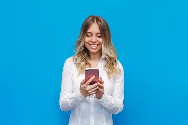 Een jonge blanke gelukkige mooie blonde vrouw in een wit kantooroverhemd glimlacht en houdt een mobiele telefoon vast die naar het scherm kijkt dat op een felle blauwe muur is geïsoleerd