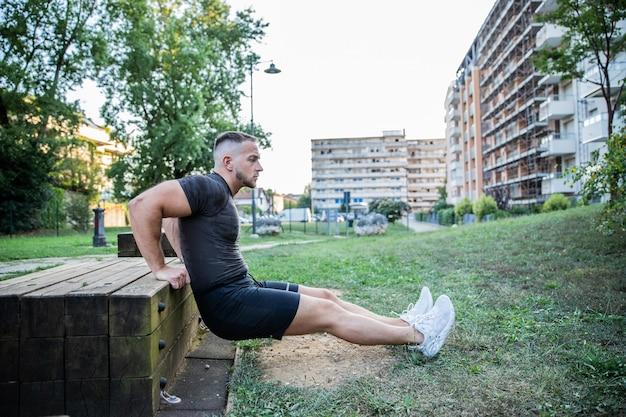 Een jonge blanke jongen voert buiten in een park verschillende spiertraining en rekoefeningen uit