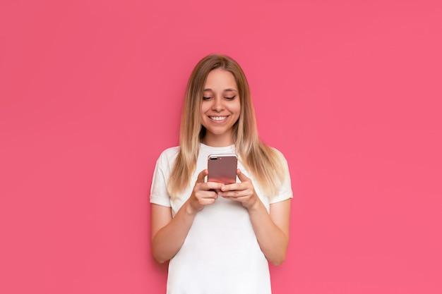 Een jonge blanke lachende mooie blonde vrouw houdt een mobiele telefoon vast en kijkt naar het scherm geïsoleerd op een felle roze muur het meisje in een witte t-shirt gebruikt haar smartphone