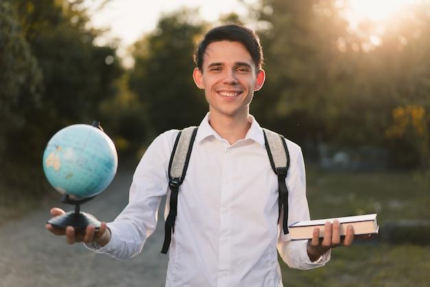 Een jonge blanke man in een wit klassiek overhemd met een grijze rugzak op zijn rug houdt in verschillende handen een wereldbol en een blauw boek vast over de natuur en het zonlicht. onderwijs concept