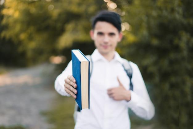 Een jonge blanke man in een wit overhemd houdt een boek voor zich en toont met zijn duim een teken voor les buiten. gemakkelijk leerconcept. zachte focus
