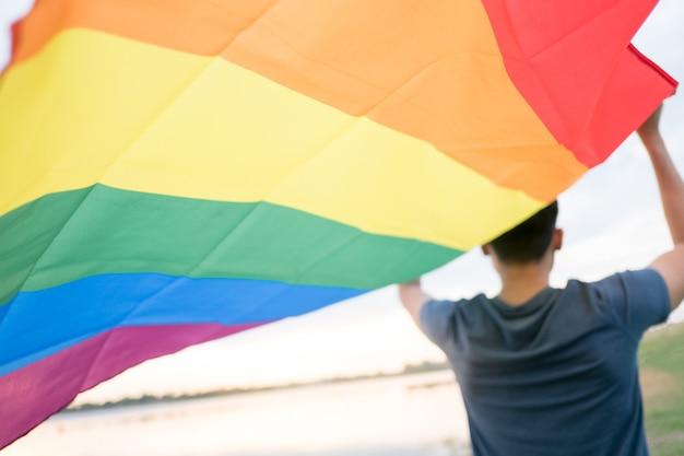 Een jonge blanke man kijkt van achteren achter een regenboogvlag boven zijn hoofd.