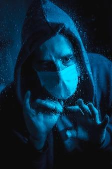 Een jonge blanke man met een masker kijkt uit het raam in de covid19 quarantaine, met blauw omgevingslicht
