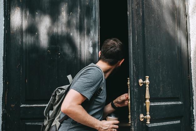 Een jonge blanke man met rugzak opent de grote houten deur naar het huis en kijkt naar binnen.