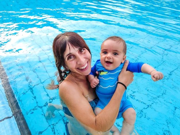 Een jonge blanke moeder die met haar baby voor het eerst in een zwembad baadt
