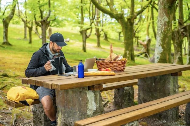 Een jonge blanke vader telewerken zittend aan een picknicktafel met computer in het bos