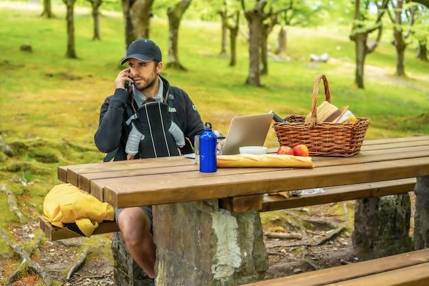 Een jonge blanke vader telewerkt aan een picknicktafel met de computer, met het kind in de rugzak