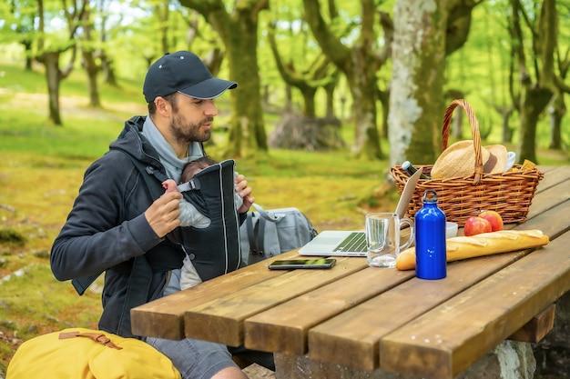 Een jonge blanke vader zwaait tijdens het videogesprek zittend aan een picknicktafel met de computer, met het kind in de rugzak