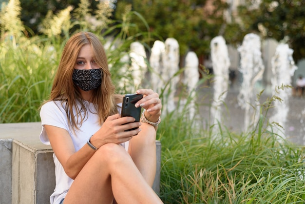 Een jonge blanke vrouw met een masker kijkt door haar telefoon in een straat