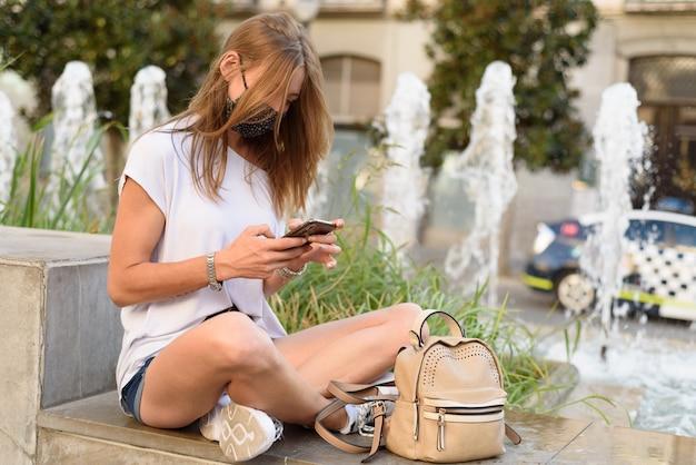 Een jonge blanke vrouw met een masker zit bij een fontein en kijkt door haar telefoon in een straat