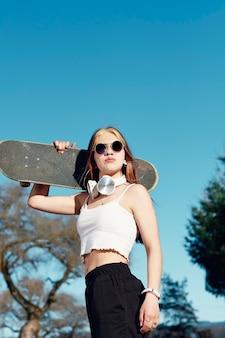 Een jonge blanke vrouw met zonnebril en koptelefoon met een skateboard over haar schouder. op de achtergrond, blauwe lucht en bomen
