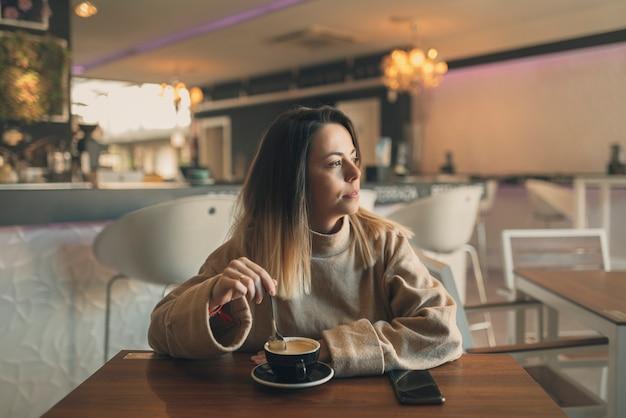 Een jonge blanke vrouw op zoek opzij in een cafetaria terwijl het drinken van een kopje koffie