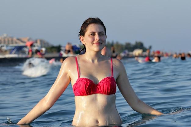 Een jonge blanke vrouw, staande taille diep in water op strand achtergrond met veel zwemmers en zonnebaden mensen en toeristen.