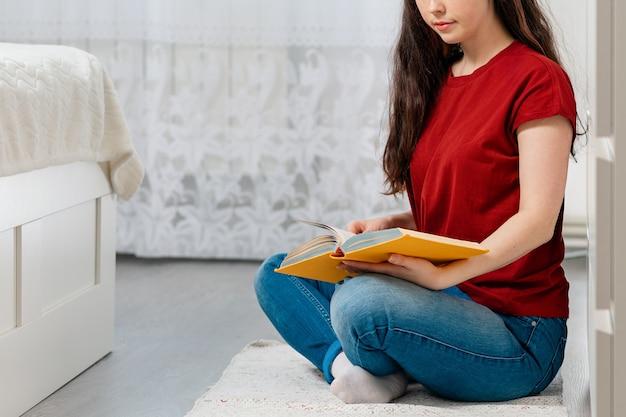 Een jonge blanke vrouw zit met gekruiste benen op de vloer een boek te lezen.