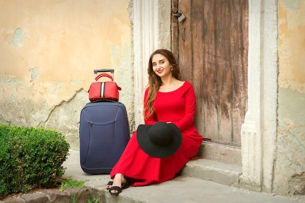 Een jonge blanke vrouw zit op de drempel van een oud huis in een rode lange jurk met koffer buiten