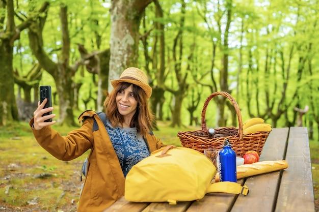 Een jonge blanke vrouw zwaait aan de telefoon zittend aan een picknicktafel in het bos