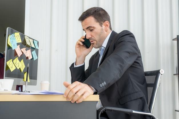 Een jonge blanke zakenman praat zelf met zijn klant