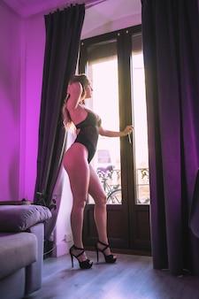 Een jonge blonde blanke in ondergoed en zwarte hakken kijkt uit het raam naast de gordijnen van zijn huis. sensuele fotografie thuis