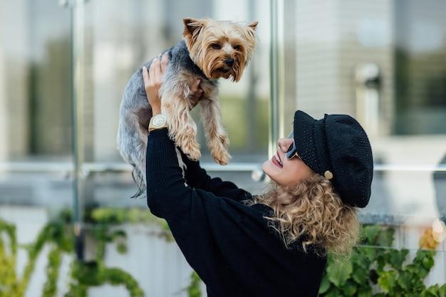 Een jonge blonde blanke vrouw houdt een kleine grappige hond vast in de armen van twee kleuren zwart-witte chihuahua. knuffels en kusjes liefde.