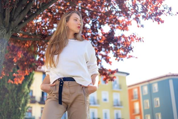 Een jonge blonde blanke vrouw poseert voor de camera in het zonlicht in de stad pamplona